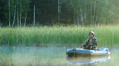 The fisherman floats on a lake on an inflatable boat with a fishing rod. Early - stock footage