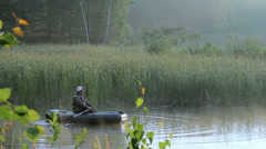 The fisherman floats on a lake on an inflatable boat with a fishing rod. Early Stock Footage