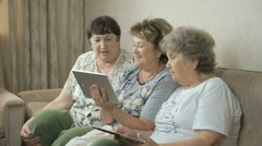 Grandmothers look at photos using digital tablets Stock Footage