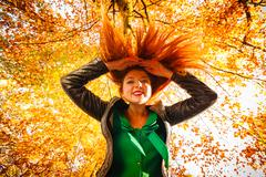 Unusual angle of young woman in autumn park - stock photo