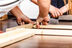 People assembling wood furniture. DIY. - stock photo