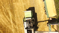 Aerial view of a combine harvester pouring wheat on a truck in a field in 4k Stock Footage
