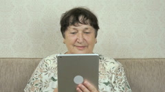 Elderly woman holding a silver digital tablet Stock Footage