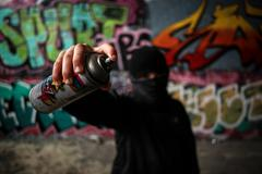 Hooded boy holding a spray paint with attitude Stock Photos