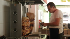 Male chef cutting gyros in fast food store by Sheyno. Stock Footage