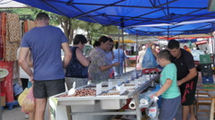 Stand with olives at market place, customer paying and taking the bag by Sheyno. Stock Footage