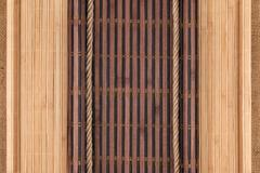 Bamboo mat twisted in the form of a manuscript and rope on sackcloth - stock photo