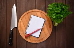 Menu concept. Cutting board on planks food background Stock Photos
