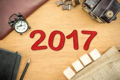 Red 2017 New year number on Wooden Table top with clock,type box,notebook,lea - stock photo