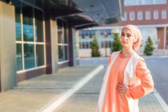 Young woman wearing hijab head scarf in city - stock photo