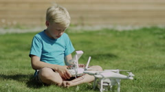 Child assembling modern drone on the green grass lawn. Putting on propellers Stock Footage