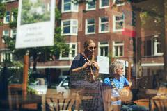Window reflections of musicians performing acoustic at outdoor cafe. Amsterda Stock Photos