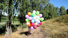Little girl with balloons running on the path along the lake. Stock Footage