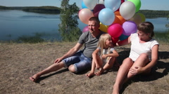 Family on vacation at the lake with helium balloons Stock Footage