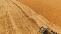 Aerial view of combine harvester bulk grain in truck in 4K Stock Footage