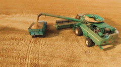 Aerial view of combine harvester bulk grain in truck on field in 4K Stock Footage