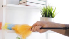 Woman with duster cleaning dust from shelf at home Stock Footage