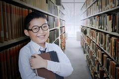 Boy holds book in the library aisle - stock photo