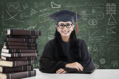 Female bachelor and books in class 1 - stock photo