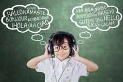 Girl learns foreign language with headphones Stock Photos