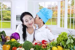 Little boy kiss his mother in the kitchen Stock Photos