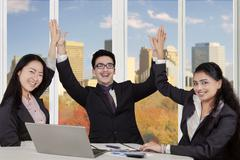 Multiracial entrepreneurs clapping hands at workplace - stock photo