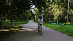 A man rides a bicycle in the park on a sunny day Stock Footage