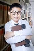 Schoolboy standing in the library aisle Stock Photos