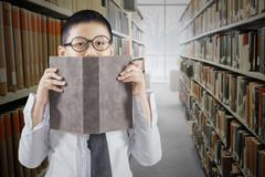 Schoolboy with book in the library aisle - stock photo