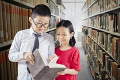 Students read books in library aisle Stock Photos