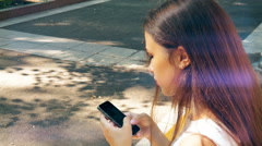 Young beautiful girl dials sms on your smartphone Stock Footage