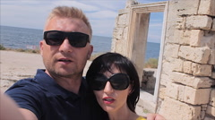 Attractive Happy Couple Taking Selfie on the ruins of the ancient city and sea Stock Footage
