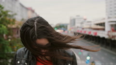Smiling girl standing on bridge touching her hair looking around then looks at Stock Footage
