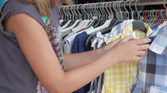 Young female customer choosing summer shirts and blouses in boutique, close up. Stock Footage