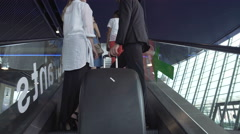 Business trip, partners arriving at conference, moving on escalator in airport Stock Footage