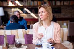 Woman in cafe drinking coffee, enjoying her espresso Stock Photos