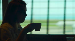 Young lady sitting in airport restaurant and enjoying hot coffee, tourism Stock Footage