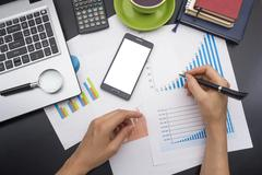 closeup of a young woman checking accounts. Office desk table with supplies top - stock photo