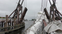 Yachts pass through historical wooden bascule bridge Stock Footage