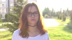 Video portrait teenage girl wearing glasses walking in the park shaking hair Stock Footage