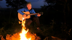 Man playing an acoustic guitar in the woods Stock Footage