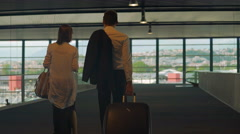 Couple in formal wear walking in airport with bags, business trip, partners Stock Footage