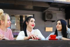 Three beautiful female smile in cafe, talk, tell secrets, eat, d Stock Photos