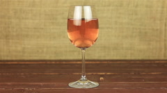 Young man drinking rose wine on wooden table Stock Footage