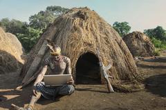 Man of the Mursi Tribe with laptop and kalashnikov gun, Omo Valley, Ethiopia - stock photo