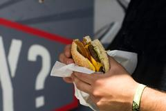 Male customer's hand eating hamburger from fast food van Stock Photos