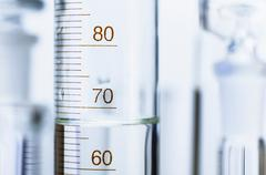 Chemical glassware. Graduated cylinder and other out-of-focus chemical lab Stock Photos