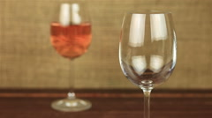 Rose wine pouring into glass on wooden table Stock Footage