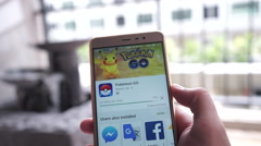 People searching for Pokemon GO in Google Play Store and install on smartphone Stock Footage