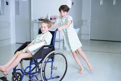 Boy patients pushing friend in wheelchair  on hospital children's ward Stock Photos